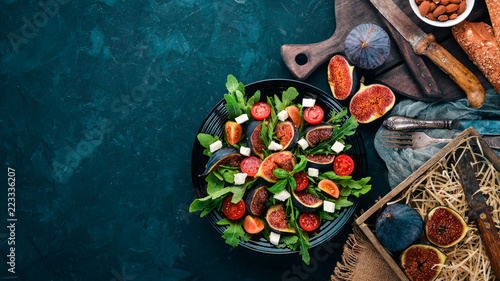 Fototapeta Fresh salad with figs, arugula leaves, cherry tomatoes and feta cheese. Free space for text. Top view.