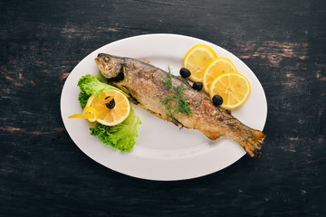 Baked Trout with Vegetables. On the old wooden background. Free space for text. Top view.