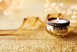 Candlelight on golden glittering background - 223364246