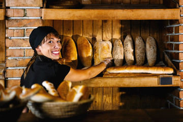 Smiling Female Bakery Assistant Working At Bakery Shop