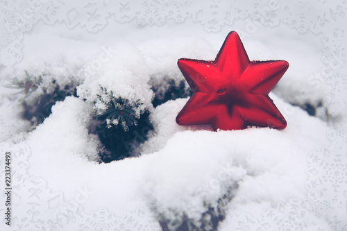 Red Christmas star on white snow. Winter background.