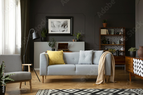 Leinwandbild Motiv Real photo of grey sofa with pillows standing in dark living room interior with molding on wall, metal lamp, vintage cupboards and window with drapes