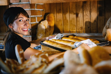Smiling Female Baker Holding Tray With Baguette