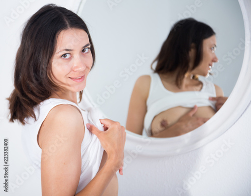 Woman topless playfully posing near mirror  in bedroom