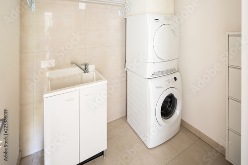 Fototapeta Laundry room with modern washer and dryer