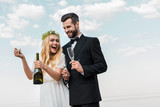 laughing bride in white dress opening champagne bottle on beach - 223389062