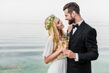 wedding couple holding glasses of champagne and looking at each other on beach - 223389276