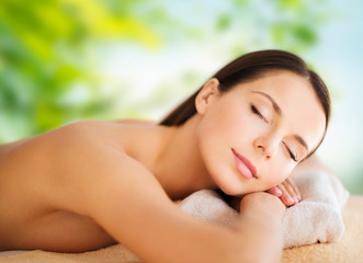 wellness, spa and beauty concept - close up of beautiful woman over green natural background © Syda Productions