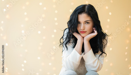 Portrait of a young woman on a shiny light background - 223394280