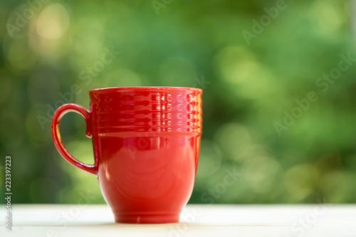 A coffee mug on a shiny green forest background - 223397223