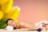 Beautiful young woman receiving hot stone massage - 223410666