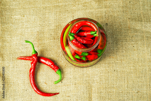 Marinated hot chili pepper in a glass jar. Home blanks - 223415800