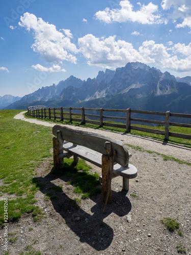 Foto Murales Hözerne Sitzbank mit Schatten vor Berggipfeln und blau weissem Himmel, 3 zinnen Bahn, Südtirol, Italien