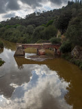 Reste einer roten Steinbrücke in stehendem Fluss mit Wolkenspiegelungen, Maremma, Italien - 223419811