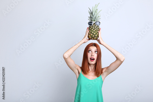 Foto Murales Beautiful redhaired woman and pineapple with sunglasses on grey background