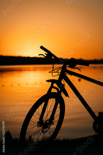 Foto Murales bicycle on the background of a sunset
