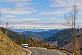Two vans on a winding mountain road - 223431413