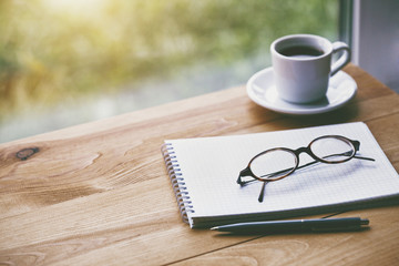 cup of fresh morning coffee with paper notebook, glasses and pen for writing © Ivan Kruk