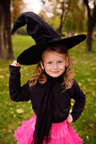 baby girl in a carnival costume and a witch's hat at a Halloween party - 223443008