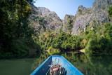 Boot auf einem Fluss mit Bergen - 223443419