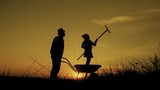 Silhouettes of father and daughter going with transportation for the land and a rake tool. Small scale organic farming concept. - 223447282