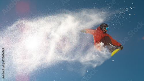 obraz lub plakat SLOW MOTION: Snowboarder jumping big air, snowflakes flying behind him in winter