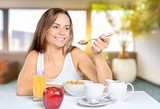 Attracive young woman enjoying tea and fruits