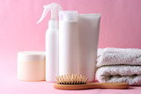 cosmetics for hair care, a hairbrush and a towel on a colored background.