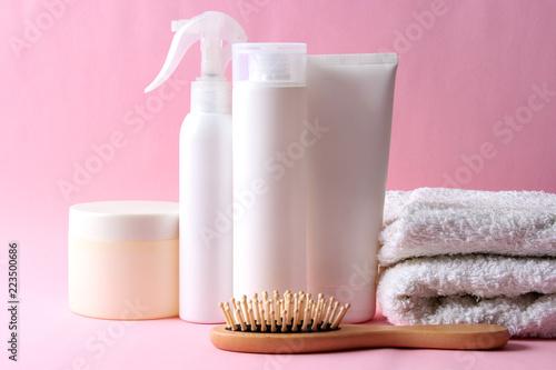 kosmetyki do pielęgnacji włosów, szczotka do włosów i ręcznik na kolorowym tle.