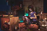 Girl in cat costume reading a book with magnifying glass in Halloween decorations - 223500844