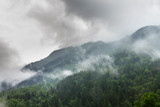 Clouds and fog in the green forest mountains in the Rhone valley near Brig and Sion in  Switzerland, on a summer morning - 223507053
