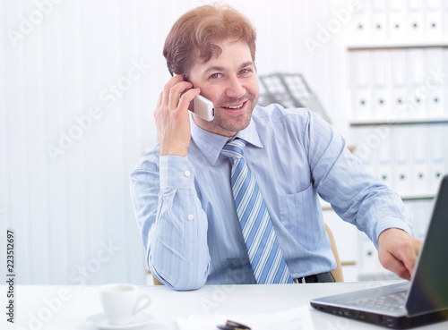 handsome businessman sitting at Desk and talking on a cell phone - 223512697