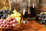 A bottle of red wine, a glass and grapes in a basket on the background of old barrels - 223513621