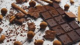 Closeup of arranged mess of black chocolate bar with milk chocolate pieces and spices on wooden table - 223518255