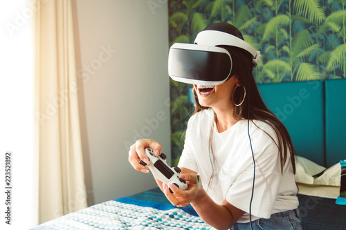 Pretty girl having fun playing videogames with virtual reality device.