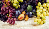 Autumn fruits and berries close-up on a wooden table.  Dessert of sweet fruit .Healthy food. Grapes and plums