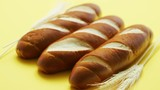 Closeup of golden baguettes with few soft wheat ears lying in row on yellow background - 223526230