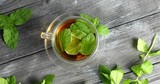 Top view of glass cup with fresh herbal tea and mint leaves on gray wooden table - 223526661