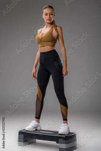 fit young woman doing step aerobics on grey