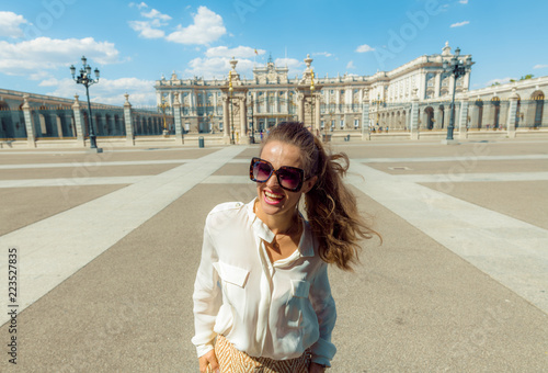happy modern tourist woman near Royal Palace in Madrid, Spain