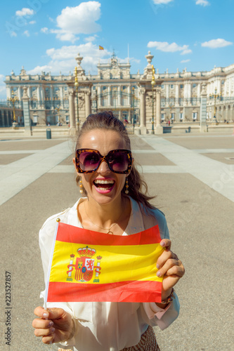 smiling woman in front of Royal Palace showing Spain flag