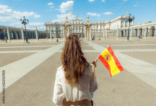 modern traveller woman with Spain flag against Royal Palace
