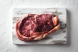 Marbling ribeye steak on white wood plate. Prime rib beef chop - 223534069