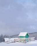Fantastic winter landscape with green wooden chapel and house in snowy mountains. Christmas holiday concept. Carpathians mountain, Ukraine, Europe - 223534815