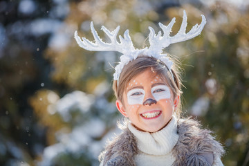 Portrait of smiling boy with funny antlers of a deer. Holiday concept.