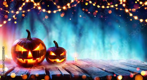 Leinwanddruck Bild Halloween Party - Pumpkins And String Lights On Table In Dark Forest