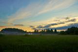 Foggy sunrise on a field with cloudy sky.