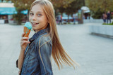 Cute and happy young girl eating ice cream outside