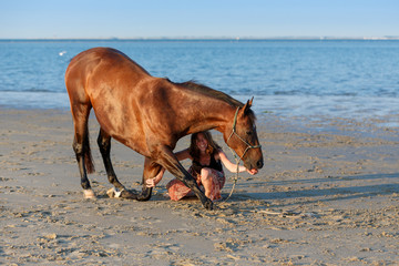 Pferd im Kompliment und Frau am Strand © Nadine Haase