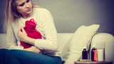 Woman feeling stomach cramps sitting on cofa - 223604620